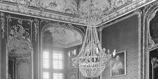Historical photography of the northwest corner of the Red Room, with stucco, mirror, and chandelier, Bruchsal Palace before its destruction.