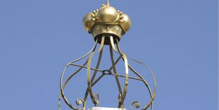 Peak of the roof with a golden crown at Bruchsal Palace.