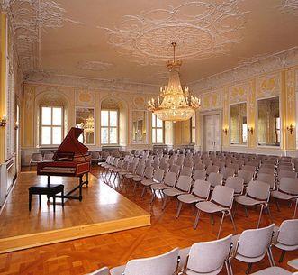 Salle de Musique de chambre avec piano à queue et rangées de sièges au château de Bruchsal; crédit photo: Staatliche Schlösser und Gärten Baden-Württemberg, ArnimWeischer