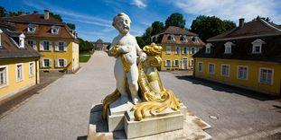 Putto am Eingang zur Gartenseite von Schloss Bruchsal mit dahinterliegenden Gebäuden, die einst als Wohnung für wichtige Hofangestellte dienten