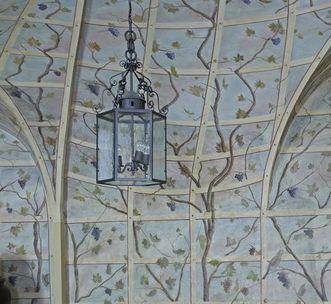 Gemalter Vogel an der Wand und Lampe im Vordergrund, Detailbild vom Laubenzimmer in Schloss Bruchsal